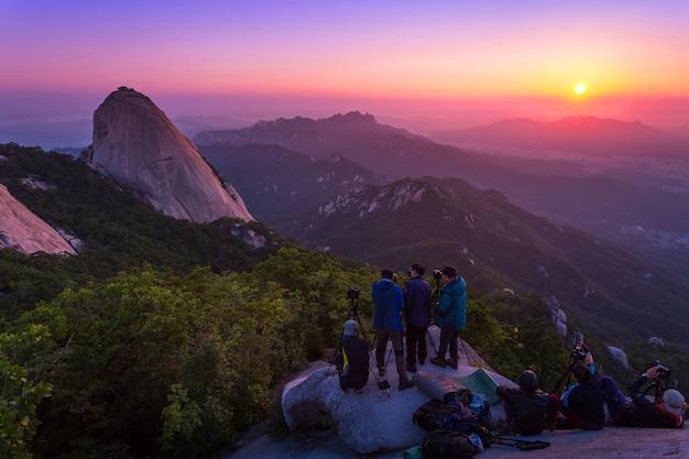 Seoul, korea - 28. juni 2015: fotograf macht ein foto des sonnenaufgangs am morgen auf buchanans bergen, seoul, südkorea.