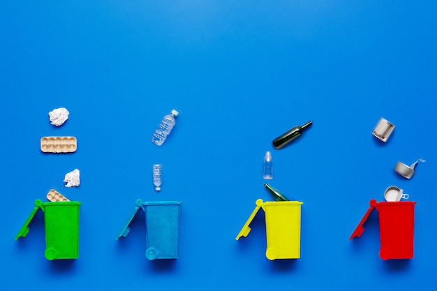Separate speicherbereinigung. mülleimer. metall und papier, kunststoff und glas. flach lag auf blauem hintergrund mit kopierraum