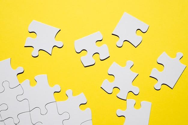 Separate weiße puzzleteil auf gelbem hintergrund