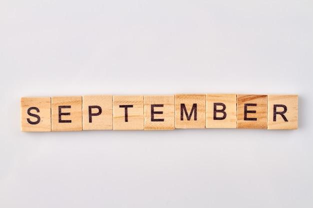 September wort geschrieben auf holzklötzen. auf weißem hintergrund isoliert.