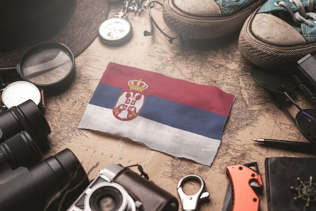 Serbien-flagge zwischen dem zubehör des reisenden auf alter weinlese-karte. touristisches bestimmungsort-konzept.