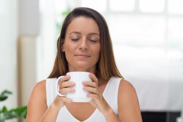 Serene junge frau genießen duft von kaffee