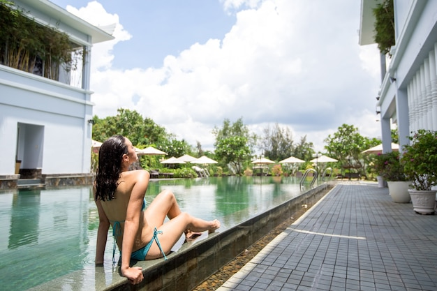 Serene junge frau sonnenbaden am hotel pool