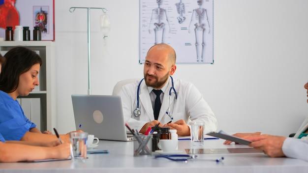 Sergeon präsentiert kollegen neue medizinische verfahren, mitarbeiter machen sich notizen und brainstorming am besprechungstisch in der krankenhausklinik. professionelles team spricht während der gesundheitskonferenz