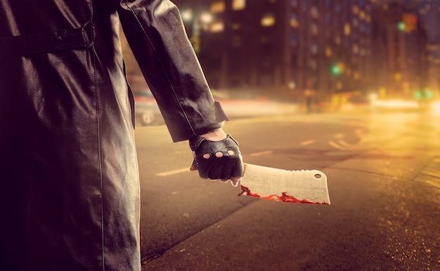 Serienmörder mit blutigem hackmesser auf der straße