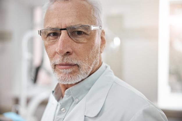 Seriöser arzt, der einen laborkittel und eine brille trägt und in die kamera schaut