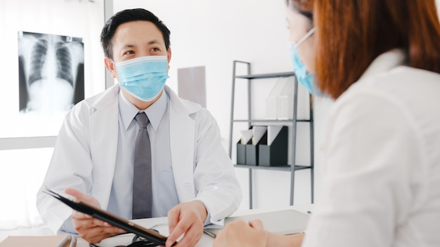 Seriöser asiatischer männlicher arzt, der eine schutzmaske mit tablet trägt, liefert großartige nachrichten und diskutiert die ergebnisse