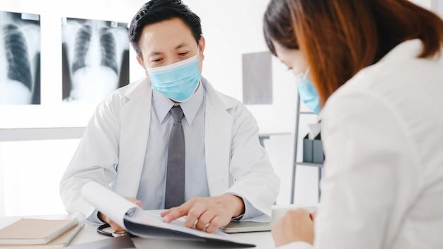 Seriöser asiatischer männlicher arzt, der eine schutzmaske mit zwischenablage trägt, liefert großartige nachrichten und diskutiert die ergebnisse