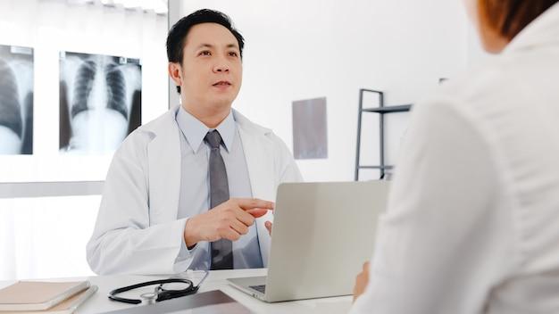 Seriöser asiatischer männlicher arzt in weißer medizinischer uniform mit computer-laptop liefert großartige nachrichten und diskutiert ergebnisse