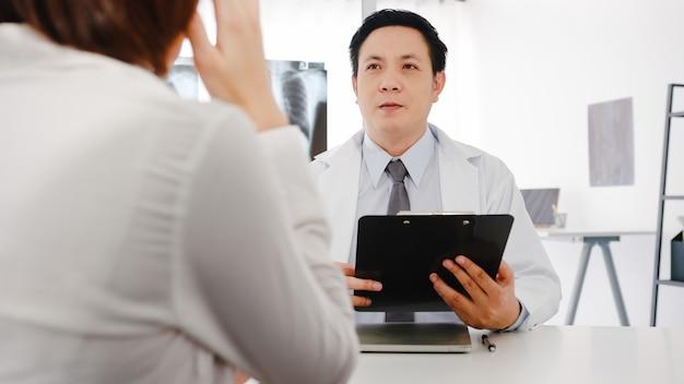 Seriöser asiatischer männlicher arzt in weißer medizinischer uniform mit zwischenablage liefert großartige nachrichten und diskutiert ergebnisse
