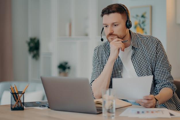 Seriöser freiberufler in freizeitkleidung, der ein dokument in der hand hält und auf den laptop-bildschirm schaut, informationen analysiert, während er online im wohnzimmer arbeitet. remote-arbeit und freiberufliches konzept