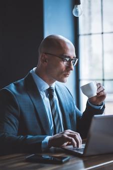 Seriöser geschäftsmann trinkt kaffee, der mit computer gegen fenster arbeitet. seitenansicht von gut