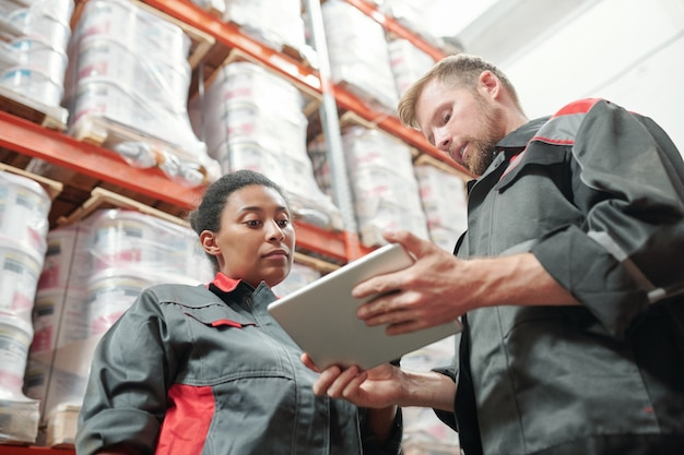 Seriöser ingenieur oder lagerarbeiter in arbeitskleidung mit tablet, während er seiner gemischtrassigen kollegin die liste der neuen waren vorstellt