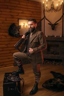 Seriöser jägermann mit alter waffe in traditioneller jagdkleidung im retrro-stil, die gegen antike brust steht.