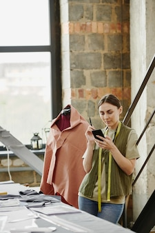Seriöser junger designer der modekollektion, der durch online-ideen blättert