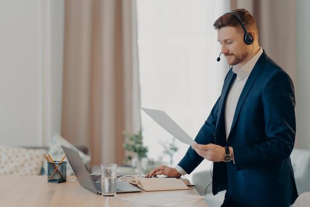 Seriöser leitende angestellter gibt präsentation des geschäftsplans hält papierdokumente steht in der nähe des desktops, der formell gekleidet ist und moderne laptops und headsets für online-konferenzen verwendet. soziale distanzarbeit