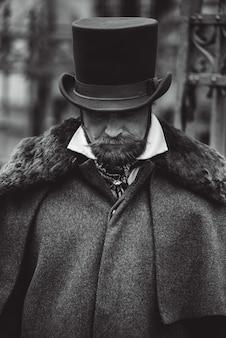 Seriöser mann mit schnurrbart in klassischer retro-kleidung, mantel und hut.