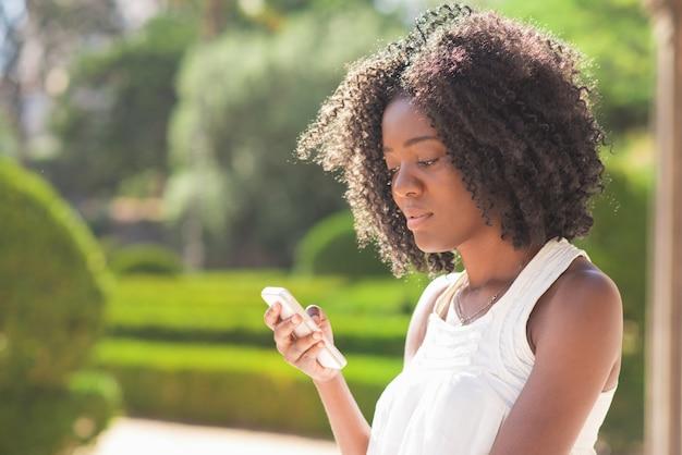 Serious black lady sms auf smartphone im park