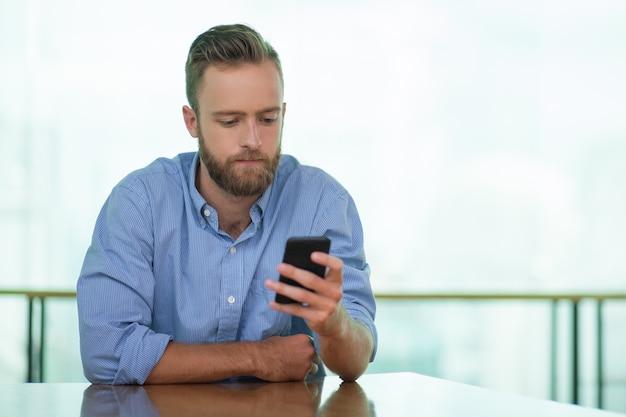 Serious junger mann mit smartphone im cafe tabelle