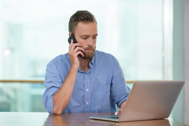Serious man anrufen über telefon und arbeiten am laptop