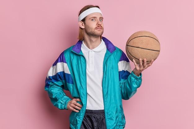 Serious man basketballspieler hält ball sieht selbstbewusst weiß stirnband sportkleidung spielt gerne lieblingsspiel.