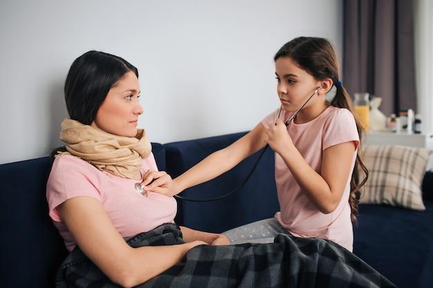 Serius kleines mädchen hört zu, wie ihre mutter durch das stethoskop atmet. sie sieht sie an und berührt die brust. junge frau schaut tochter an. sie sitzen zusammen auf der couch im zimmer.