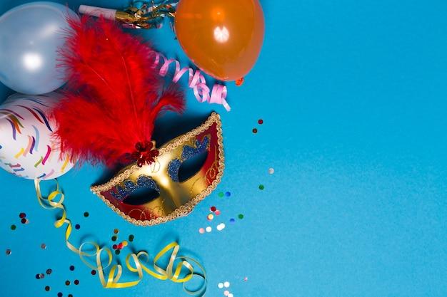 Serpentine streamer und ballons in der nähe von maske