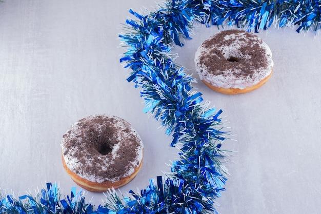Serpentinenanordnung von girlande und zwei donuts auf weißer oberfläche