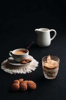Serradura dessert und heißer kaffee mit einigen keksen und einem dunklen hintergrund