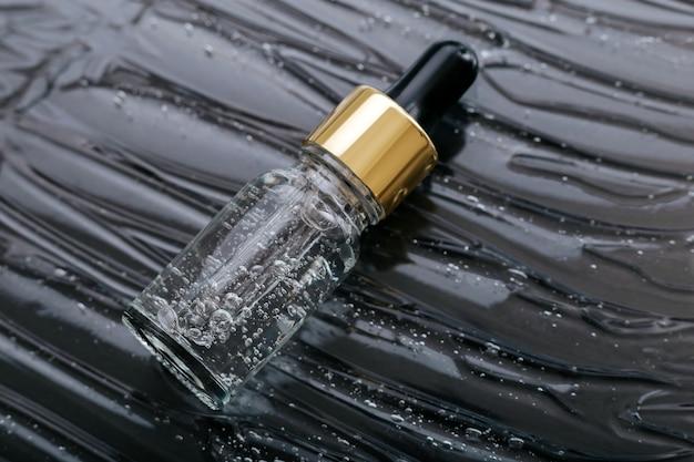 Serum auf flüssigem gel oder hyaluron-kollagenserum in tropfer auf schwarzem wasserwellen-texturhintergrund. pipettenflasche für kosmetisches hautpflegeprodukt. kosmetik gesundheit gesicht schönheit der haut.