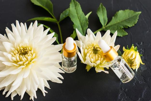 Serum für die gesichtspflege in kosmetikflaschen mit einer pipette auf dem hintergrund einer schönen dahlie.