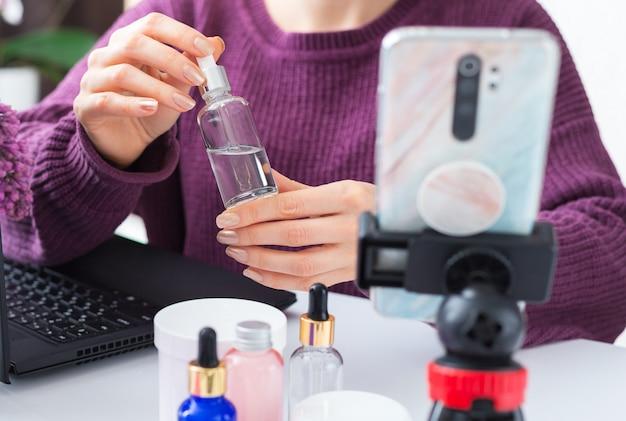 Serum in weiblichen händen der schönheitsbloggerin. kosmetikerin online-aufzeichnung von videoinhalten, live-überprüfung von kosmetikprodukten. kosmetologietraining, hautpflege-tutorial für dermatologen