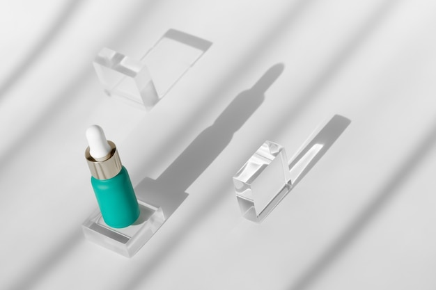 Serum mit peptiden und retinol auf modernen transparenten acrylblöcken mit sonnenschatten, kosmetisch