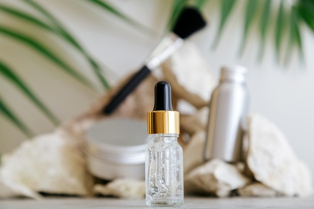 Serum transparentes gel für kosmetische gesichtspflegeprodukte, medizinische kosmetik hyaluronsäure in tropfer mit pipetten auf hellem hintergrund. natürliche herrenkosmetik. serum vor steinsockel.