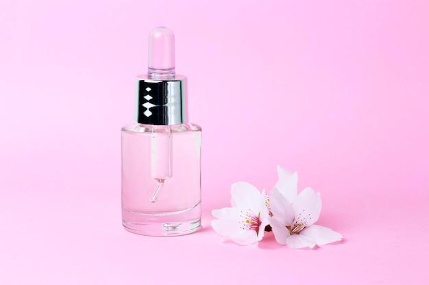 Serum und tropfenzähler auf einer rosa hintergrundnahaufnahme, naturkosmetikkonzept