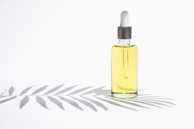 Serumflasche auf weißem hintergrund trendiger schatten von einem palmzweig kosmetikmodell platz zum einfügen von textbildern