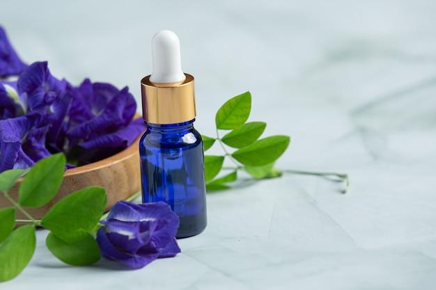 Serumflasche butterfly pea flower oil auf weißem marmorhintergrund