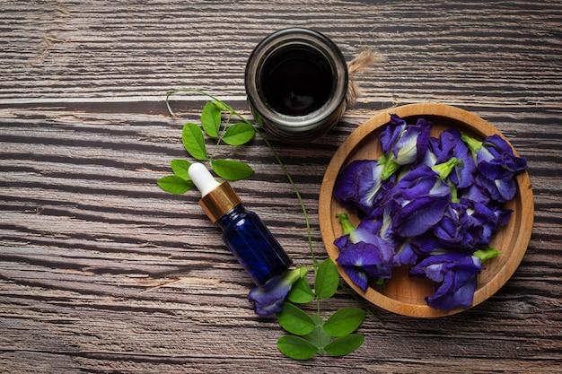 Serumflasche des schmetterlingserbsenblumenöls auf hölzernen hintergrund gesetzt
