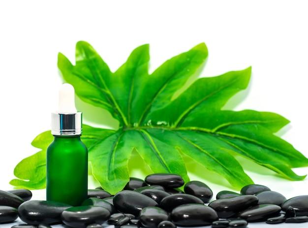 Serumölflaschentropfenmodell oder ätherisches öl auf schwarzem stein gegen grünes blatt auf weißem hintergrund