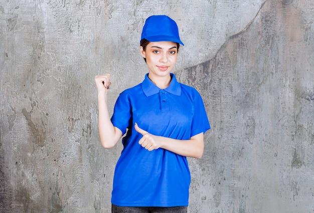 Service-agentin in blauer uniform, die etwas dahinter zeigt.