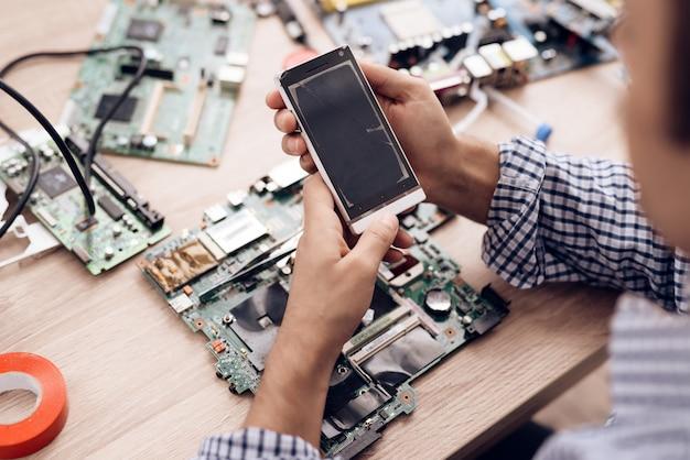 Service-arbeiter halten in der hand und sieht defektes telefon aus