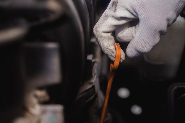 Servicemann, der den autoölmotor überprüft, den ölprüfstab oder den ölmessstab in der nähe hält