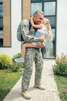 Servicemann, der emotional ist. soldat in uniform, der sich emotional fühlt, während er seine weinende glückliche tochter umarmt