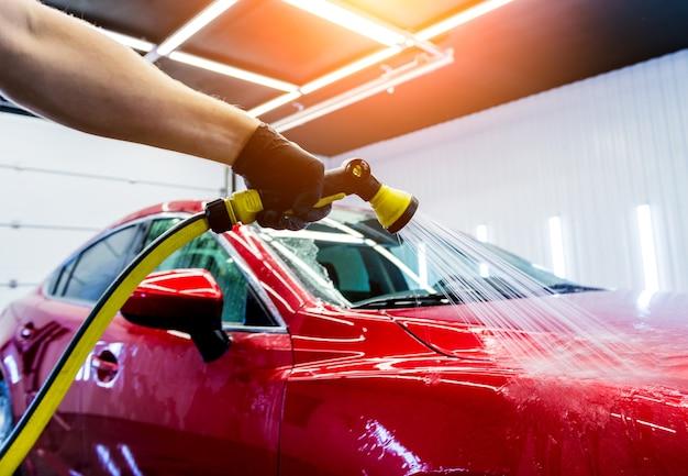 Servicemitarbeiter, der auto auf einer autowäsche wäscht.