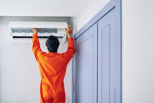 Servicemitarbeiter, der die klimaanlage im haus installiert, blick von hinten