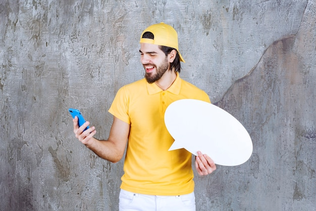 Servicemitarbeiter in gelber uniform, der eine ovale infotafel hält und einen videoanruf tätigt