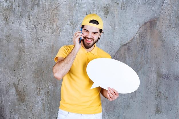 Servicemitarbeiter in gelber uniform, der eine ovale infotafel hält und mit dem telefon spricht