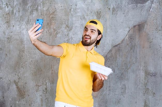 Servicemitarbeiter in gelber uniform, der eine plastikbox zum mitnehmen hält und ein selfie macht.
