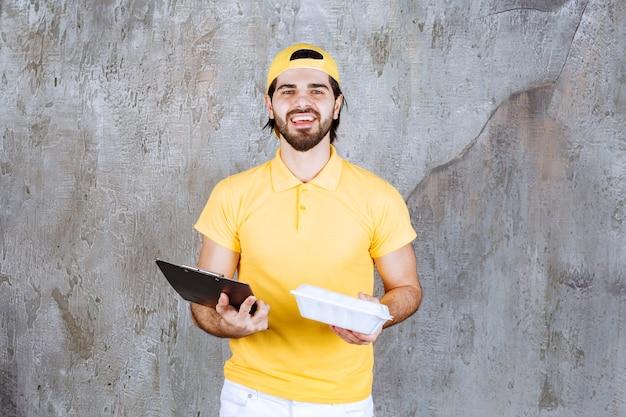 Servicemitarbeiter in gelber uniform mit einer plastikbox zum mitnehmen und einem schwarzen ordner.