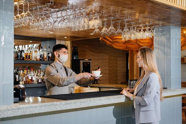 Servieren eines maskierten barista köstlichen natürlichen kaffees an ein junges mädchen in einem schönen café während einer pandemie.